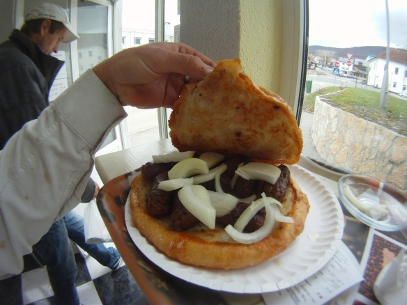 Cevapi, greasy sausage links and onions between two Croatian pancakes
