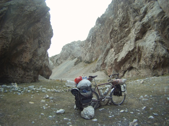 Packing up to leave valley where I built rock walls to protect from wind, large rocks are propping up Gaby