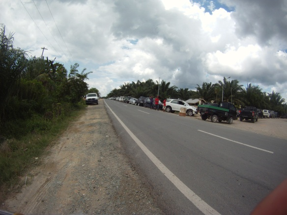 Line of cars waiting at a remote jungle gas station